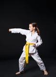 空手道衣服的儿童女孩与黄色传送带展示姿态 免版税库存图片