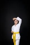 空手道衣服的儿童女孩与黄色传送带展示姿态 免版税库存照片