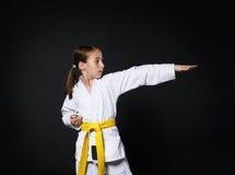 空手道衣服的儿童女孩与黄色传送带展示姿态 库存图片