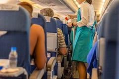 空服员对乘客的服务饮料在船上 免版税库存照片