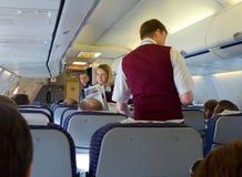 空服员给乘客新鲜的新闻 免版税库存照片
