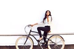 给空气亲吻的自行车的时兴的少妇 免版税库存照片