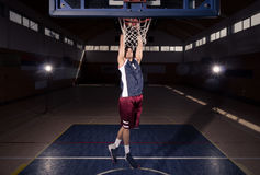 空气灌篮的,户内篮球场一个蓝球运动员 免版税库存图片