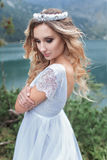 空气神仙的蓝色婚礼礼服的美丽的柔和的女孩新娘与在山的豪华卷毛在有冠的u湖附近 免版税库存图片