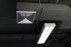 空气管道箱子、空调、空气管道,空气透气和荧光灯电灯泡在修造的选择聚焦里面 免版税库存图片
