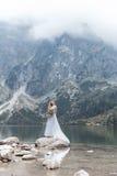 空气蓝色新娘婚礼礼服的美丽的精美女孩与在山的豪华卷毛在有婚礼bou的湖附近 库存照片