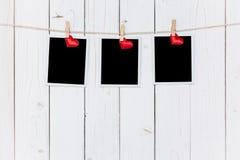 空白三张照片的框架和垂悬在与空间的白色木背景的红色心脏 免版税库存图片