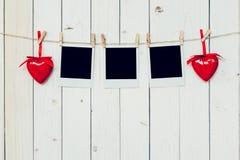 空白三张照片的框架和垂悬在白色木头后面的红色心脏 库存图片