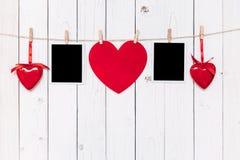 空白两张照片的框架和垂悬在白色木backgr的红色心脏 库存照片