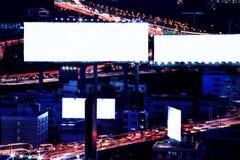 空白广告牌在与城市交通的晚上和汽车点燃 免版税库存照片