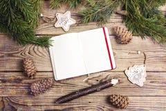 空白开放笔记本、杉木分支、雪松锥体和装饰 库存照片