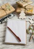 空白开放笔记薄,圣诞节礼物,木表面上的糖果 免版税库存照片