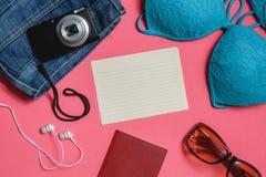 空白支票名单,护照,泳装,牛仔裤,太阳镜,在桃红色背景的照片照相机 顶视图旅行概念 图库摄影