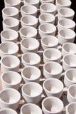 空白杯子行从黏土的 库存照片