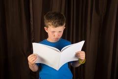 读空白的书或杂志的年轻男孩 免版税图库摄影