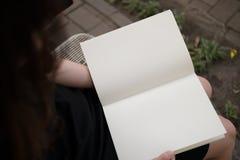 读空白的书的妇女在庭院里 库存照片
