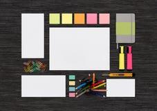 空白的五颜六色的文具嘲笑顶视图在黑办公室de 库存图片