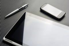 空白的企业说谎在有反射的一种片剂旁边的智能手机和笔在碳背景上 免版税图库摄影