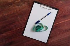 空白的剪贴板、笔和测量的磁带在桌上 库存图片