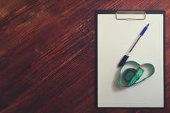空白的剪贴板、笔和测量的磁带在桌上 免版税库存照片