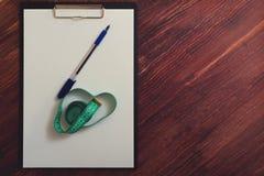 空白的剪贴板、笔和测量的磁带在桌上 库存照片