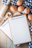 空白的剪贴板用在木背景的鸡蛋 顶视图 免版税库存图片