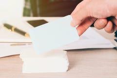 空白的名片在被弄脏的办公桌背景为嘲笑联络id信息设计模板在手中使用我们 免版税库存照片