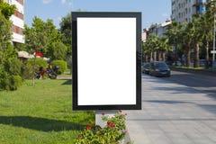 空白的嘲笑在城市背景的垂直的街道海报广告牌 免版税库存照片