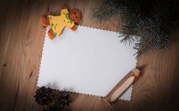 空白的圣诞卡、姜饼和铅笔在木backgrou 免版税图库摄影