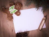 空白的圣诞卡、姜饼和铅笔在木backgroun 免版税库存照片