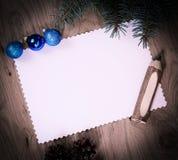 空白的圣诞卡、杉木锥体和铅笔在木backgroun 免版税库存照片