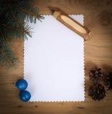 空白的圣诞卡、杉木锥体和铅笔在木backgroun 免版税库存图片