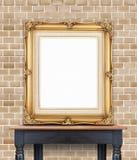 空白的在苍白橙色砖墙的葡萄酒金黄照片框架倾斜 免版税库存照片
