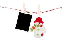 空白的垂悬在晒衣绳的照片框架和雪人 图库摄影