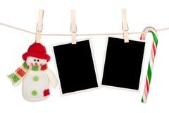 空白的垂悬在晒衣绳的照片框架和雪人 库存图片