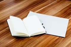 空白的报纸和开放笔记本在一张棕色木桌上 免版税图库摄影