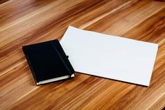 空白的报纸和笔记本在一张棕色木桌上 免版税库存图片