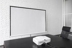 空白的放映机帆布在办公室 免版税库存图片