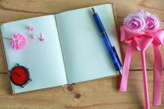 空白的日志笔记本、桃红色花、手表和笔在木桌上 免版税库存图片