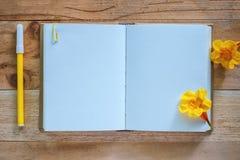 空白的日志笔记本、黄色花和笔在木桌上 库存图片