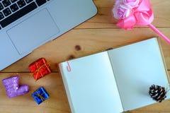 空白的日志笔记本和个人计算机的膝上型计算机有圣诞节和新年装饰品的和装饰在木桌上 免版税库存图片
