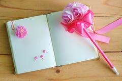 空白的日志笔记本和桃红色花在木桌上 免版税图库摄影