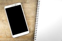 空白的智能手机和笔记本在木桌上 免版税库存照片