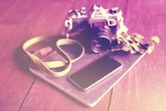空白的智能手机屏幕、老牌照相机和日志在木fl 库存照片