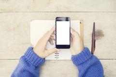 空白的智能手机屏幕用妇女手,空白的日志和笔, m 免版税库存图片