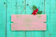空白的桃红色风化了与垂悬在古色古香的绿色木门的红色花的标志 免版税库存照片