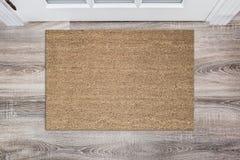 空白的棕褐色在白色门前上色了粗硬纤维擦鞋垫在大厅里 在木地板,产品大模型上的席子 免版税库存照片