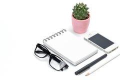 空白的模板螺旋白色笔记本笔记薄,在罐,眼睛玻璃,铅笔,智能手机的仙人掌隔绝了白色背景 免版税库存图片