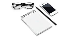 空白的模板螺旋白色笔记本笔记薄,玻璃,铅笔,智能手机隔绝了白色背景 免版税图库摄影