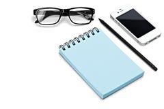 空白的模板螺旋蓝色笔记本笔记薄,玻璃,铅笔,智能手机隔绝了白色背景 免版税库存图片